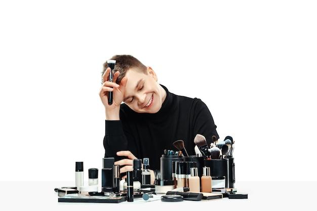 Maquiador profissional com ferramentas isoladas no fundo branco do estúdio. o homem na profissão feminina. conceito de igualdade de gênero