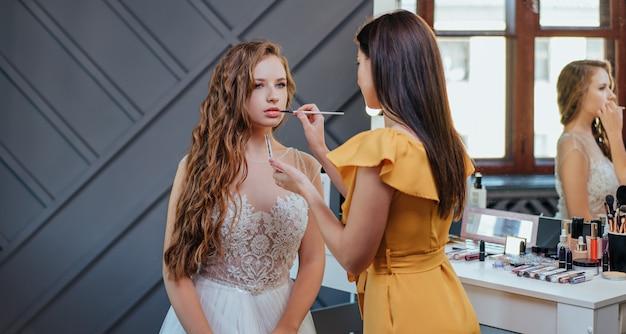 Maquiador profissional de maquiagem e penteado, fazendo maquiagem para a noiva. cosméticos profissionais