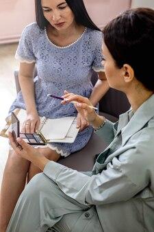 Maquiador profissional ensinando cliente do sexo feminino a aplicar blush no rosto e usar pincel na masterclass