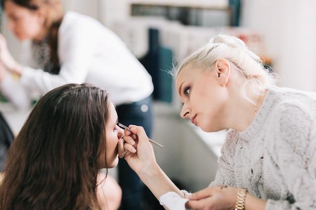 Maquiador profissional faz maquiagem para uma jovem. o conceito de estilo de vida