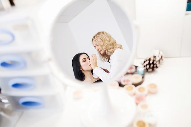 Maquiador profissional fazendo maquiagem de modelo de glamour no trabalho