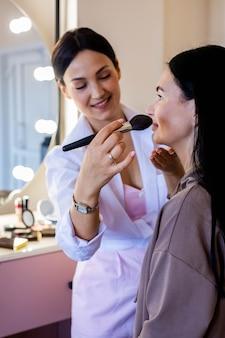 Maquiador profissional feliz aplicando lápis labial de cosméticos em cliente mulher trabalhando no salão de beleza
