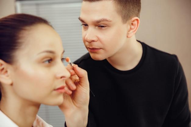 Maquiador profissional trabalhando com mulher jovem e bonita. o homem na profissão feminina. conceito de igualdade de gênero
