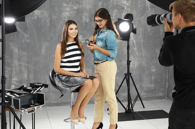 Maquiador profissional trabalhando com uma jovem mulher bonita em sessão de fotos