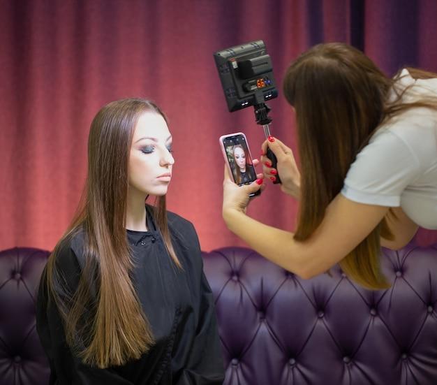 Maquiador tira fotos da modelo depois do trabalho