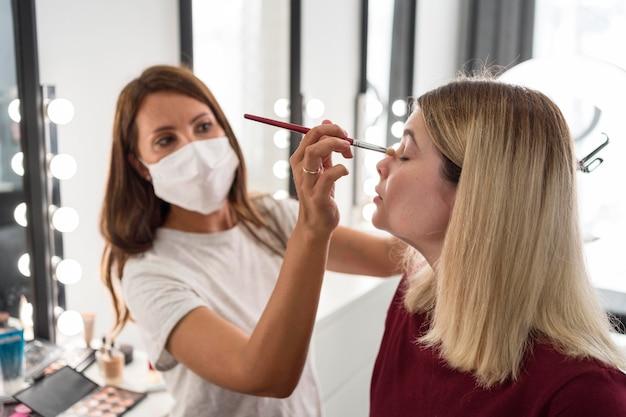 Maquiador usando máscara médica, vista lateral