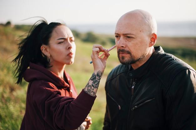 Maquiadora de menina bonita trabalhando com homem barbudo em jaqueta de couro
