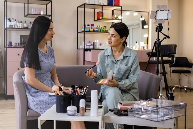 Maquiadora profissional ensinando mulher aplicando cosméticos no rosto em estúdio de beleza
