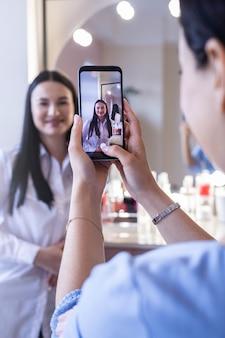Maquiadora profissional tirando foto de uma cliente feliz aplicando maquiagem