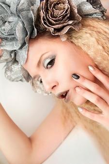 Maquiagem bege cinza prata e manicure para o modelo de meninas fecham com cabelos ondulados.