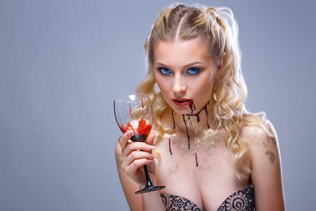 Maquiagem brilhante no rosto de uma linda mulher segurando um copo de vinho na mão