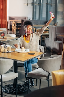Maquiagem brilhante positiva mulher afro-americana sorridente com maquiagem brilhante acenando para a amiga