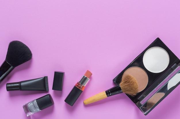 Maquiagem com cosméticos decorativos e smartphone em fundo rosa