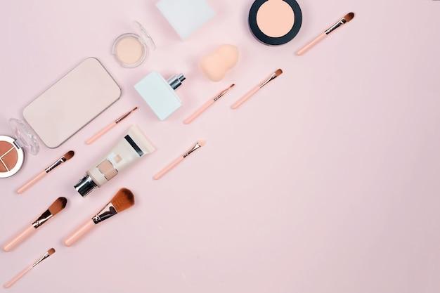 Maquiagem cosméticos decorativos, pincéis, ferramentas e acessórios em fundo rosa pastel.