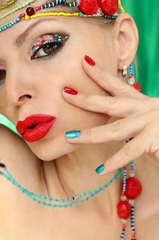 Maquiagem criativa e manicure em uma garota com joias de miçangas