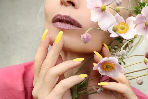 Maquiagem da moda e manicure amarela em unhas compridas
