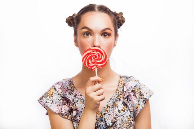 Maquiagem da moda. retrato de beleza garota segurando pirulito colorido. lábios vermelhos quentes. unhas bem cuidadas com verniz. cuidados com a pele. isolado em fundo branco