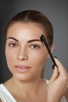 Maquiagem de beleza. cuidado de sobrancelhas. mulher bonita formando sobrancelhas com o pente. corrigindo e contornando as sobrancelhas.