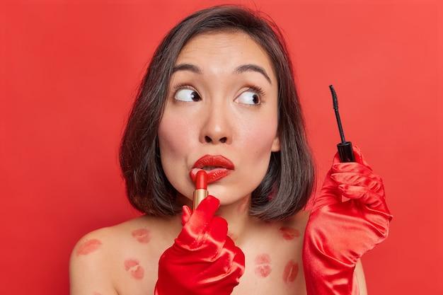 Maquiagem de beleza. mulher asiática aplica batom e rímel usa cosméticos decorativos para um visual fabuloso usa luvas vermelhas poses sem roupa contra a parede brilhante do estúdio se prepara para uma ocasião especial