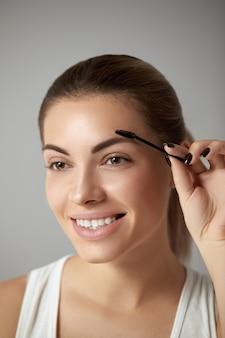 Maquiagem de beleza. mulher bonita em forma de sobrancelha closeup. modelo de menina com maquiagem profissional usando escova de sobrancelhas e sorrindo