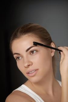 Maquiagem de beleza. mulher dando forma à sobrancelha closeup. modelo de menina com maquiagem profissional contornando as sobrancelhas