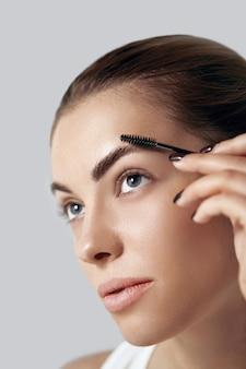 Maquiagem de beleza. mulher dando forma ao close up da sobrancelha. modelo de menina com maquiagem profissional contornando as sobrancelhas