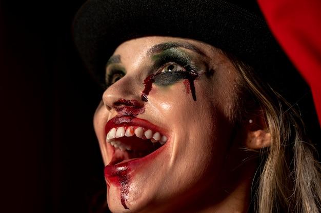 Maquiagem de mulher como um palhaço assustador ri