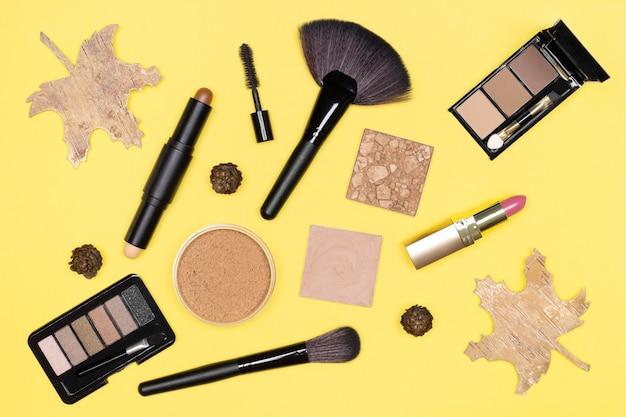 Maquiagem de outono plana lay produtos de maquiagem marrom bronze dourado cores com decorações de outono