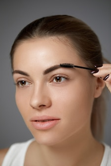 Maquiagem de sobrancelha. bela modelo formando sobrancelhas com closeup de lápis de sobrancelha.