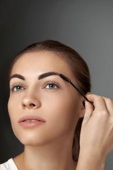 Maquiagem de sobrancelha. modelo de beleza modelando as sobrancelhas com pincel close up