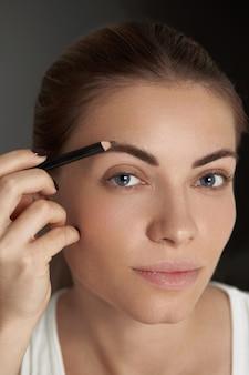 Maquiagem de sobrancelha. modelo de beleza modelando sobrancelhas com lápis de sobrancelha