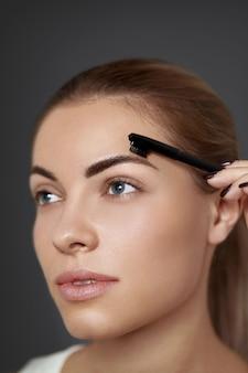 Maquiagem de sobrancelha. mulher bonita formando sobrancelhas com pente closeup. modelo de menina bonita com maquiagem profissional contornando as sobrancelhas