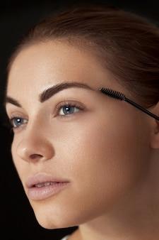 Maquiagem de sobrancelha. mulher bonita formando sobrancelhas com pincel de sobrancelha closeup