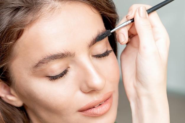 Maquiagem de sobrancelhas para mulher com ferramenta de pincel de sobrancelha.