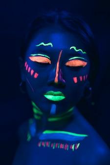 Maquiagem de tinta uv no rosto de mulher