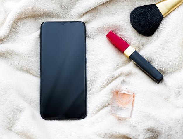 Maquiagem e celular em cobertor branco em maquete de flatlay de smartphone de inverno como modelo de aplicativo e sutiã ...