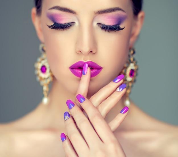 Maquiagem estilosa em tons de roxo, cílios pretos impecáveis e lábios bem formados coloridos em violeta