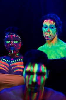 Maquiagem fluorescente colorida em homens e mulheres