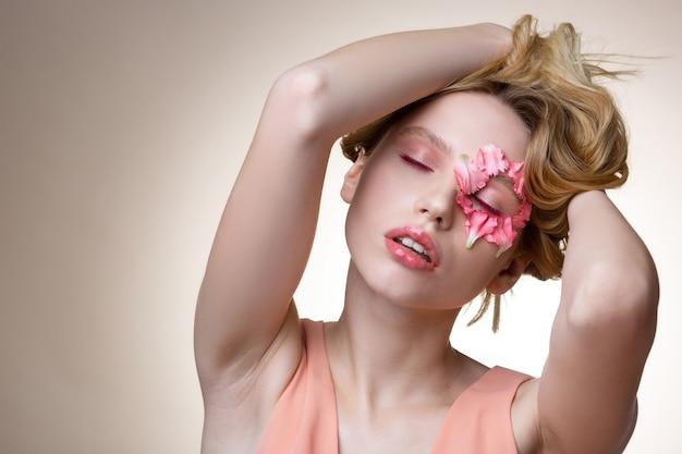 Maquiagem incrível. modelo atraente e terno fechando os olhos, mostrando uma maquiagem incrível e pétalas ao redor dos olhos