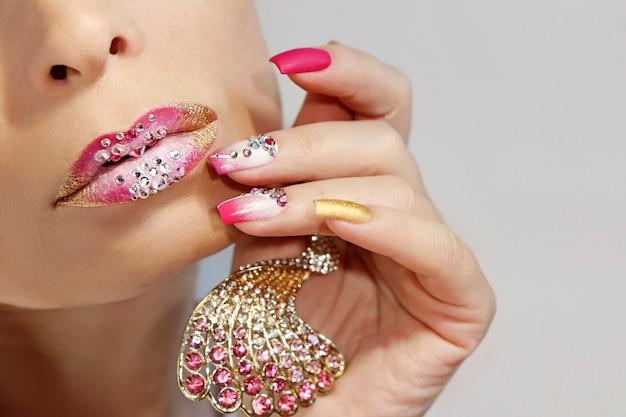 Maquiagem labial rosa e branca e manicure com strass