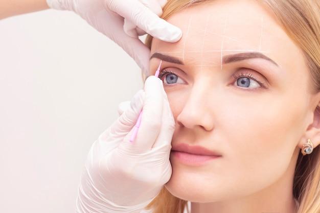 Maquiagem. mãos de esteticista fazendo tatuagem de sobrancelha no rosto de mulher. maquiagem permanente sobrancelha no salão de beleza.