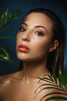 Maquiagem molhada. estilo de fotografia de moda. mulher nua em folhas.