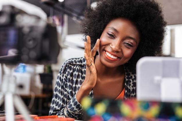 Maquiagem. mulher bonita de pele escura com maquiagem brilhante e bonita enquanto aplica blush nas bochechas