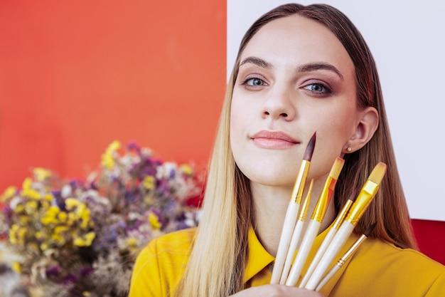 Maquiagem natural. artista loira com maquiagem natural segurando pincéis de pintura em pé perto de uma parede vermelha