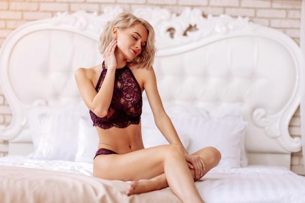 Maquiagem natural. mulher bonita com bela maquiagem natural, usando cueca, sentada na cama