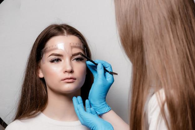 Maquiagem permanente para sobrancelhas de mulher bonita com sobrancelhas grossas no salão de beleza. esteticista closeup fazendo tatuagem sobrancelha.