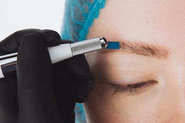 Maquiagem permanente para sobrancelhas. sobrancelha microblading. esteticista fazendo tatuagem de sobrancelha para rosto feminino. linda garota em um salão de beleza