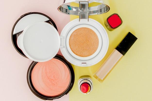 Maquiagem produtos derramando sobre um amarelo e rosa brilhante