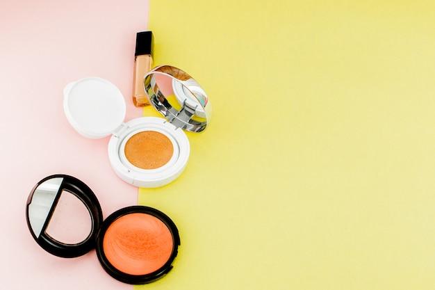 Maquiagem produtos derramando sobre um fundo amarelo e rosa brilhante com espaço de cópia