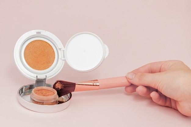 Maquiagem produtos derramando sobre um fundo rosa brilhante com espaço de cópia